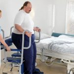 arjohuntleigh-hygiene-systems-shower-chairs-caregiver-with-patient-on-carmina