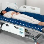 arjohuntleigh-products-therapeutic-surfaces-acute-care-active-therapy-range-nimbus-professional-deflated-mattress-on-enterprise-bed-female-patient